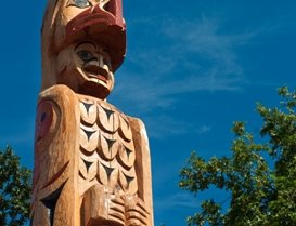 The top of a totem pole with blue sky and green trees