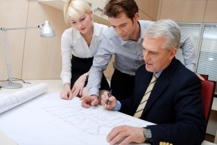 Three office workers looking over design plans on a desk