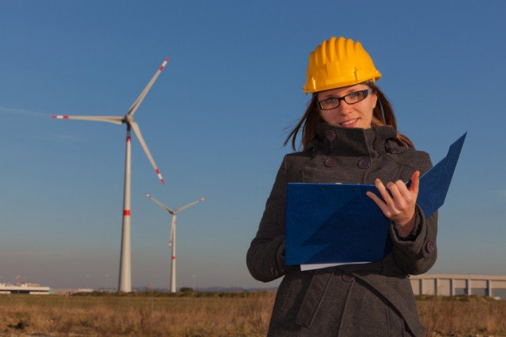 Woman with a hardhat on writing in a notebook at a wind farm