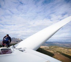Man working upon wind turbine, over 80 meters of high in a wind farm.
