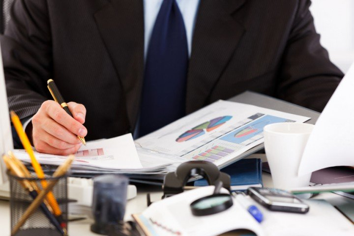 Close up of a work desk with charts and a business man working on a report