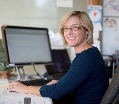 Woman smiling over her shoulder while sitting at her desk in a bright office