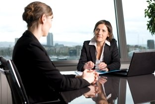 Two business women talking at a meeting table in a highrise