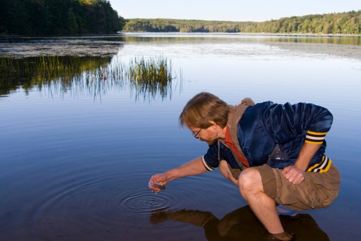 Man crouching down while standing in a pond to take a water sample