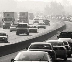 Cars driving down a busy freeway with exhaust in the air