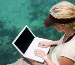 Woman working on a laptop by the ocean