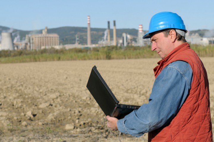 Man with a hardhat on holding a laptop with a refinery in the background