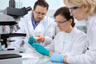 Three scientists with gloves on working with samples and microscopes